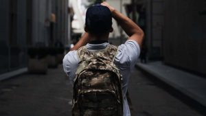 A boy taking pictures military backpack